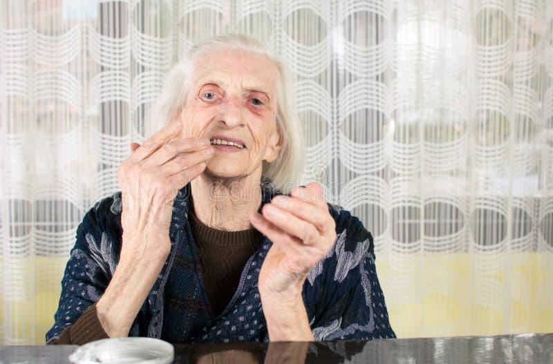 Starsza kobieta stosuje twarzy śmietankę obrazy stock