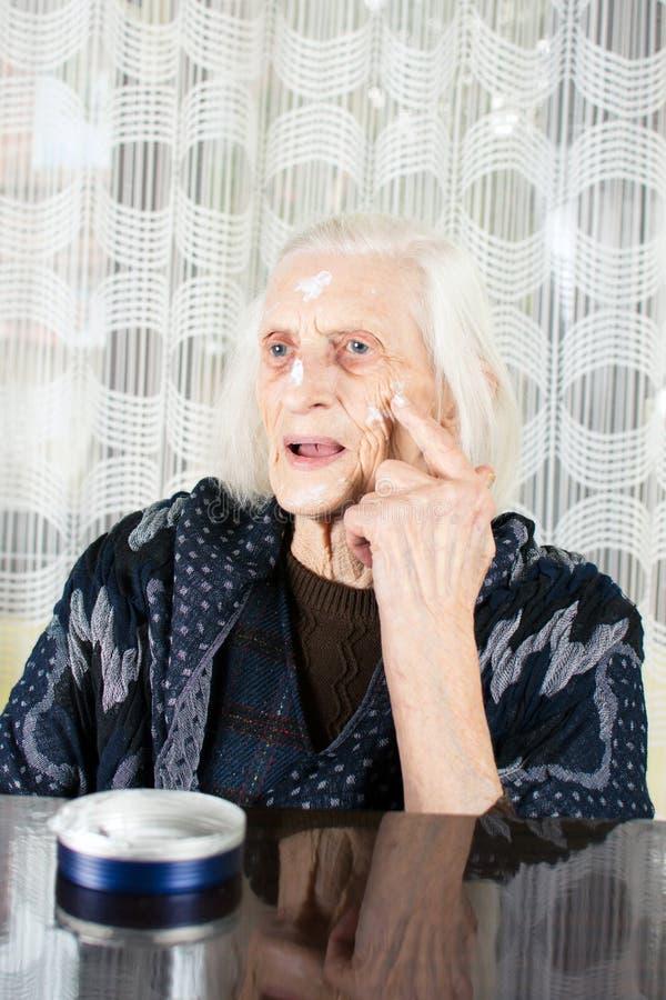 Starsza kobieta stosuje twarzy śmietankę zdjęcie stock