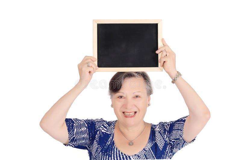Starsza kobieta trzyma emty chalkboard obraz royalty free