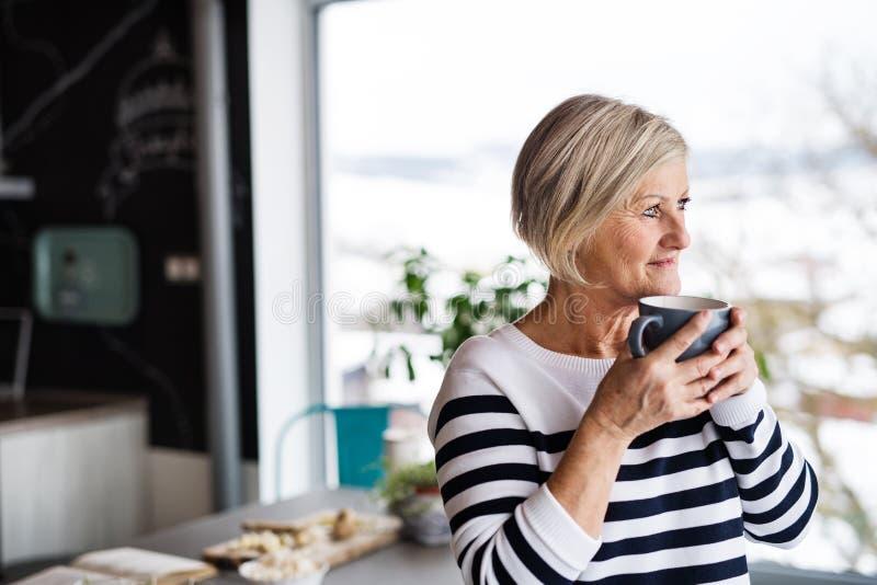 Starsza kobieta trzyma filiżankę kawy w kuchni obrazy stock