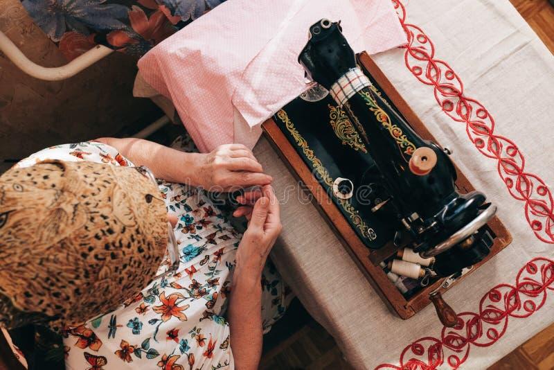 Starsza kobieta używa rocznik szwalną maszynę fotografia stock