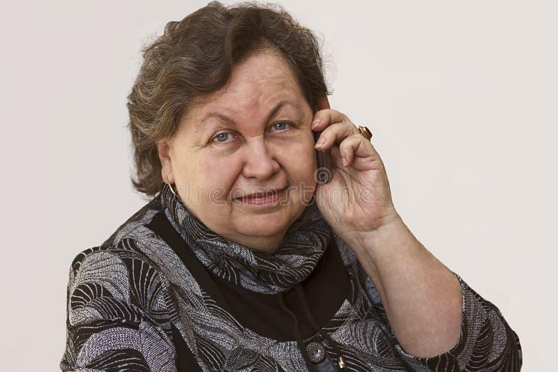 Starsza kobieta uśmiecha się opowiadać na telefonie obraz stock
