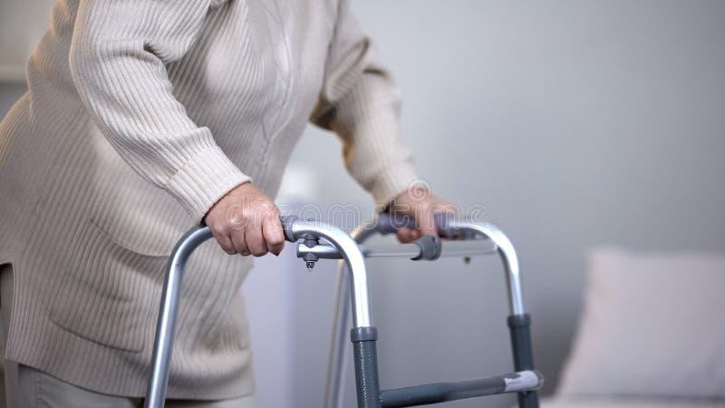 Starsza kobieta u?ywa chodz?c? ram?, rehabilitacja po ??cznego urazu, zako?czenie w g?r? obrazy royalty free