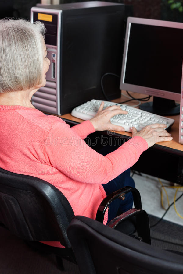 Starsza kobieta Używa komputer Przy biurkiem W sala lekcyjnej zdjęcie stock