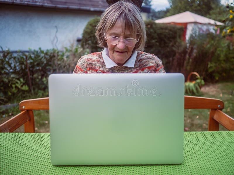 Starsza kobieta używa laptop w ogródzie obraz royalty free