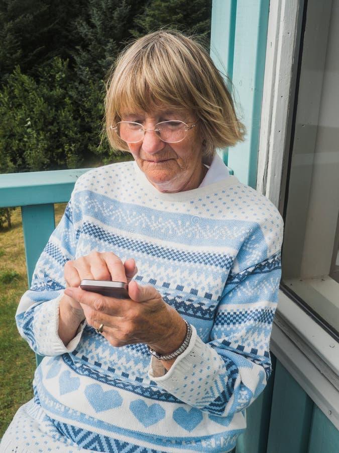Starsza kobieta używa mądrze telefon outdoors zdjęcia royalty free