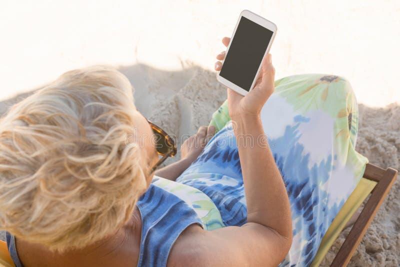 Starsza kobieta używa mądrze telefon przy plażą podczas gdy siedzący na krześle zdjęcia stock