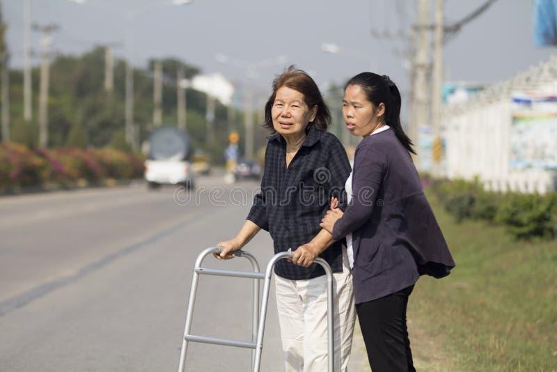Starsza kobieta używa piechura krzyża ulicę obrazy stock