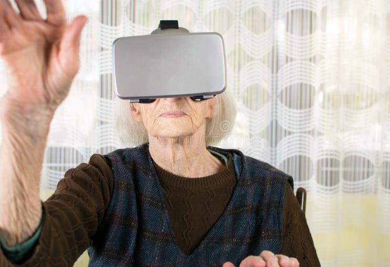 Starsza kobieta używa rzeczywistość wirtualna gogle obraz stock