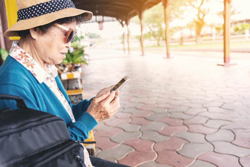 Starsza kobieta używa telefon komórkowego w dworcu zdjęcie royalty free