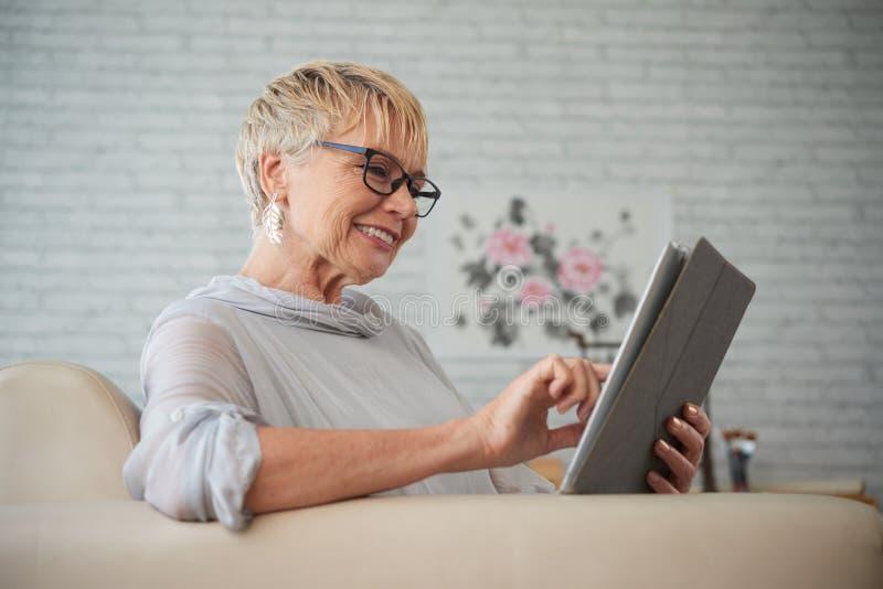 Starsza kobieta u?ywa pastylka komputer osobistego zdjęcie royalty free