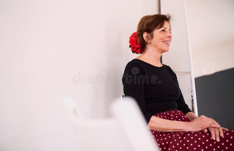 Starsza kobieta uczęszcza dancingową klasę w domu kulturym, siedzi obraz stock