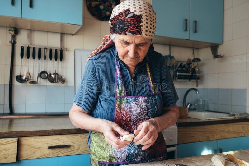 Starsza kobieta ugniata ciasto w ona domowa kuchnia obrazy stock