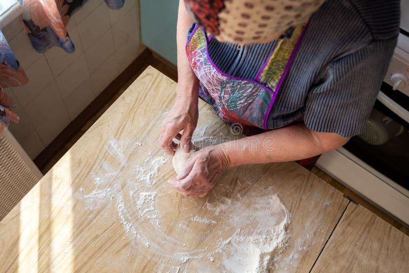 Starsza kobieta ugniata ciasto w ona domowa kuchnia zdjęcia royalty free