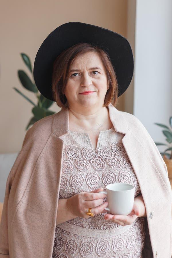 Starsza kobieta w kapeluszowym pobliskim okno w nowożytnym mieszkania wnętrzu, pije kawę zdjęcie royalty free