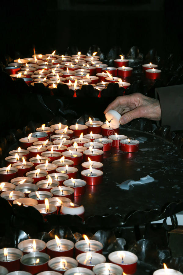 Starsza kobieta w modlitwie i zaświecająca świeczka w kościół obrazy royalty free