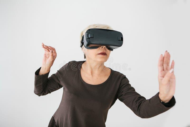 Starsza kobieta w rzeczywistość wirtualna szkłach Starsza osoba używa nowożytną technologię zdjęcia royalty free