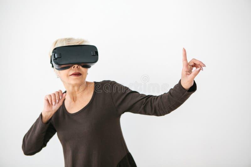 Starsza kobieta w rzeczywistość wirtualna szkłach Starsza osoba używa nowożytną technologię fotografia royalty free