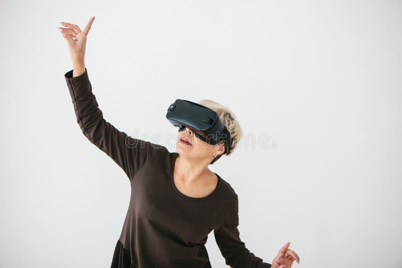 Starsza kobieta w rzeczywistość wirtualna szkłach Starsza osoba używa nowożytną technologię obrazy stock