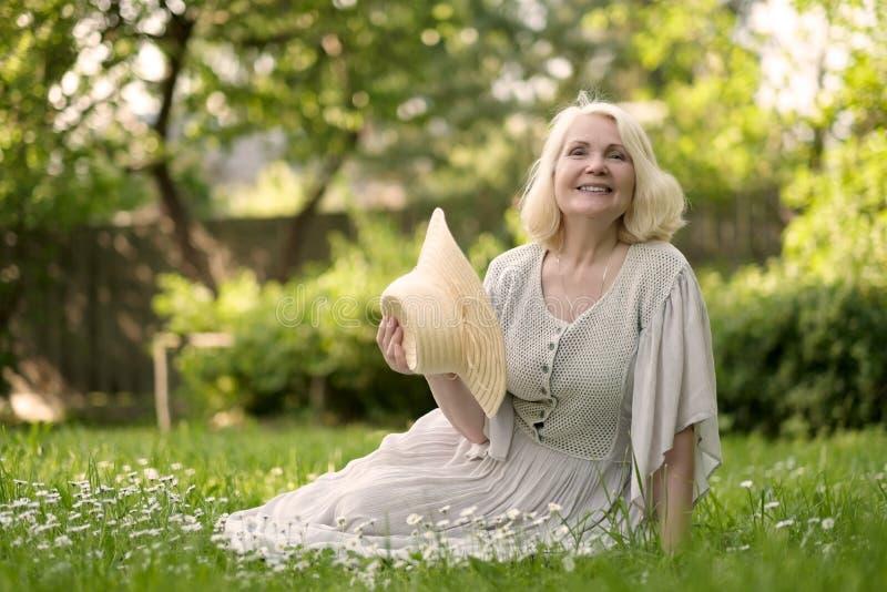 Starsza kobieta w smokingowym obsiadaniu na trawie przy parkiem zdjęcie royalty free