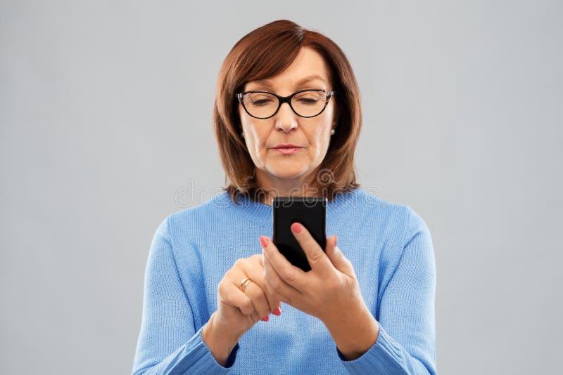 Starsza kobieta w szkłach używać smartphone fotografia royalty free