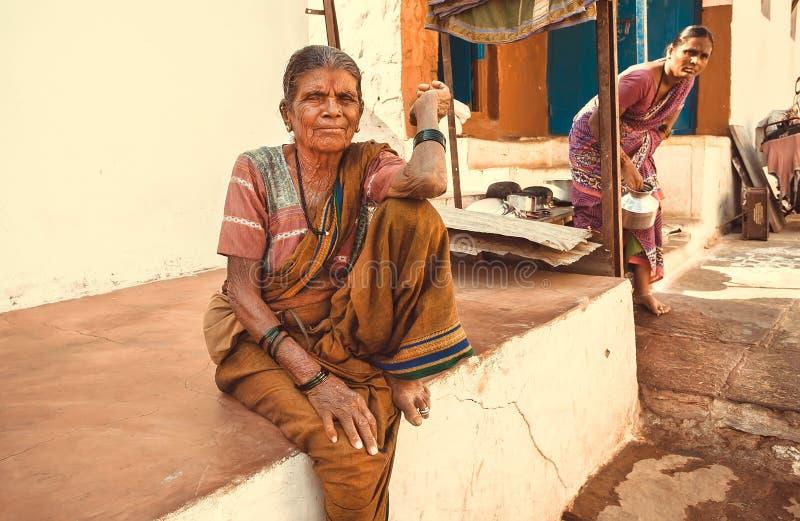 Starsza kobieta w tradycyjnym smokingowym siedzącym pobliskim wiejskim domu w indyjskiej wiosce zdjęcia royalty free