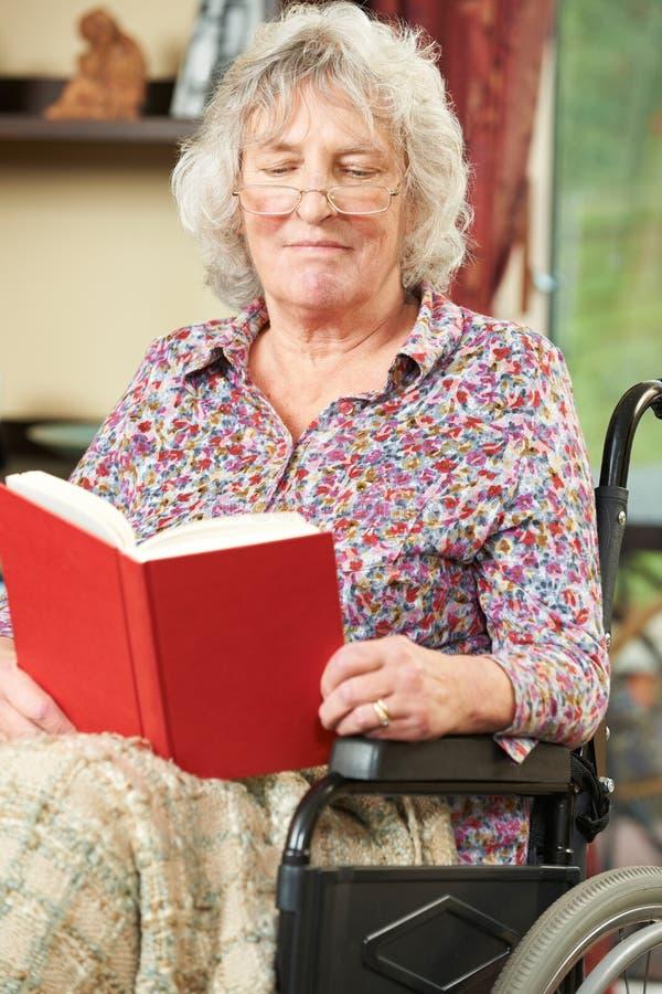 Starsza kobieta W wózek inwalidzki Czytelniczej książce zdjęcia stock