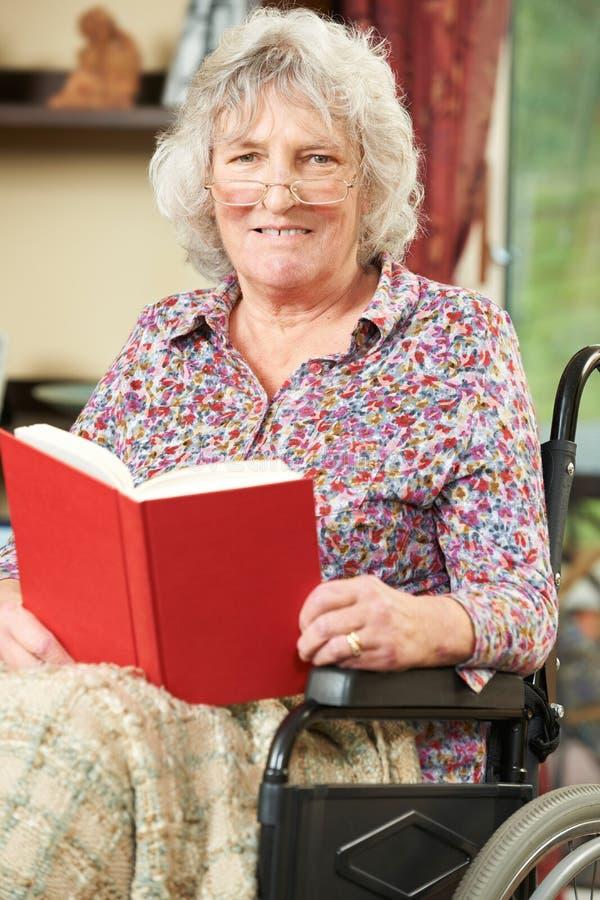 Starsza kobieta W wózek inwalidzki Czytelniczej książce fotografia royalty free