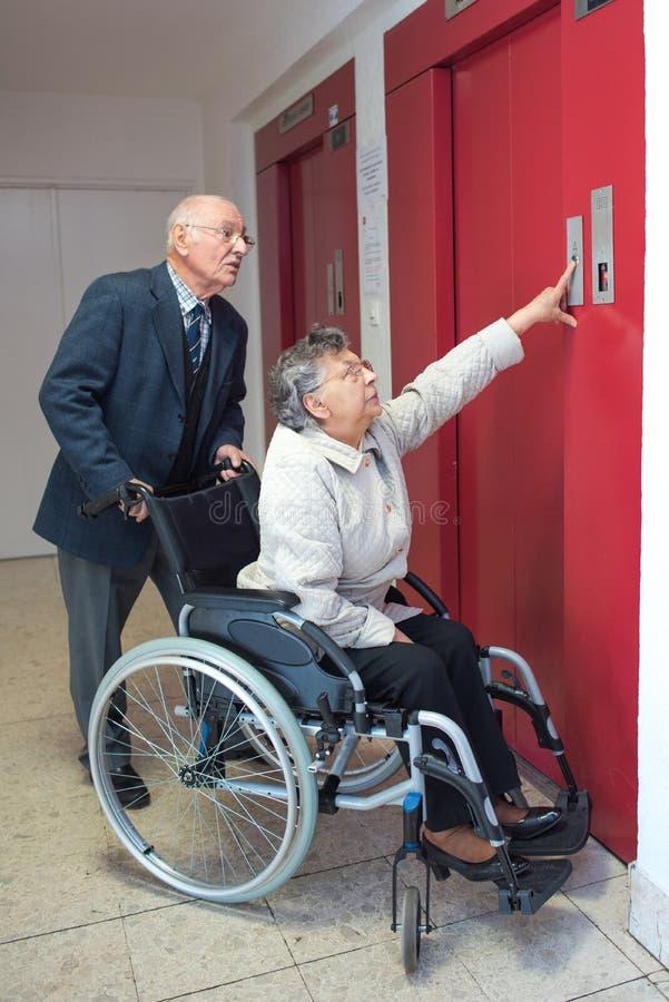 Starsza kobieta w wózka inwalidzkiego dojechaniu dla dźwignięcie guzika zdjęcie stock
