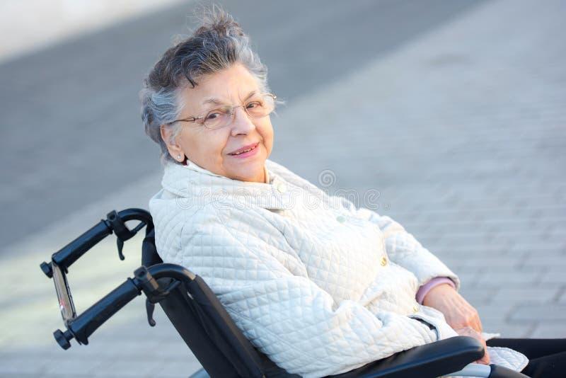 Starsza kobieta w wózka inwalidzkiego pozować obraz stock