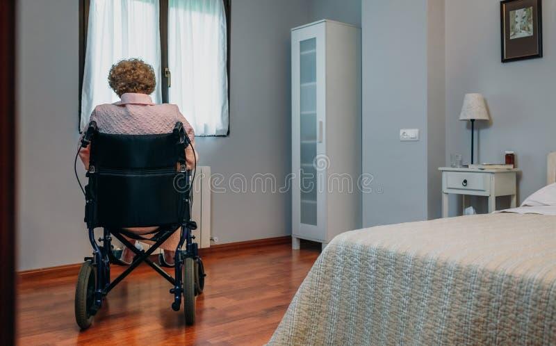 Starsza kobieta w wózku inwalidzkim samotnie obraz royalty free