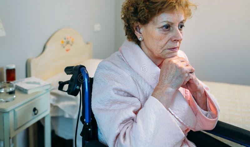 Starsza kobieta w wózku inwalidzkim samotnie fotografia stock