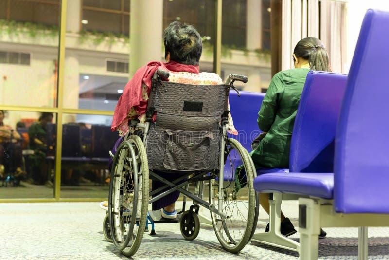 Starsza kobieta w wózku inwalidzkim z córką przy wyjściową bramą obraz royalty free