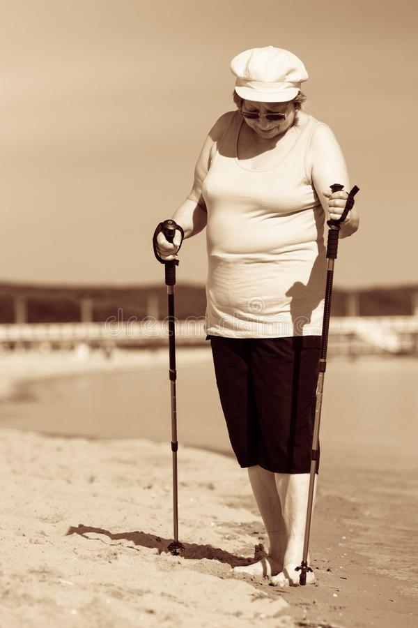 Starsza kobieta ?wiczy p??nocnego odprowadzenie na pla?y zdjęcia stock