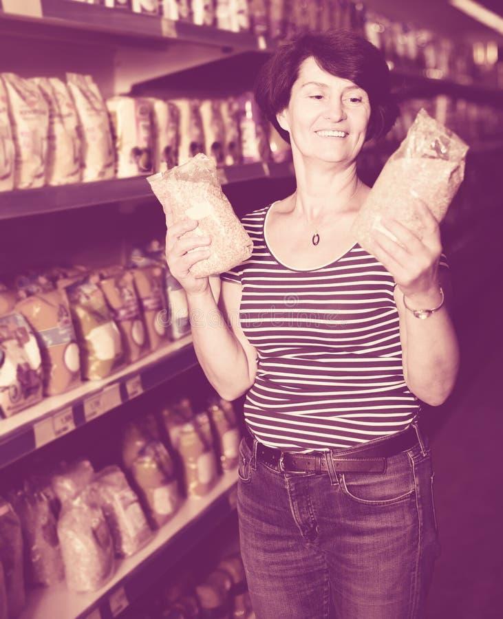 Starsza kobieta wybiera groats przy sklepem spożywczym zdjęcia royalty free