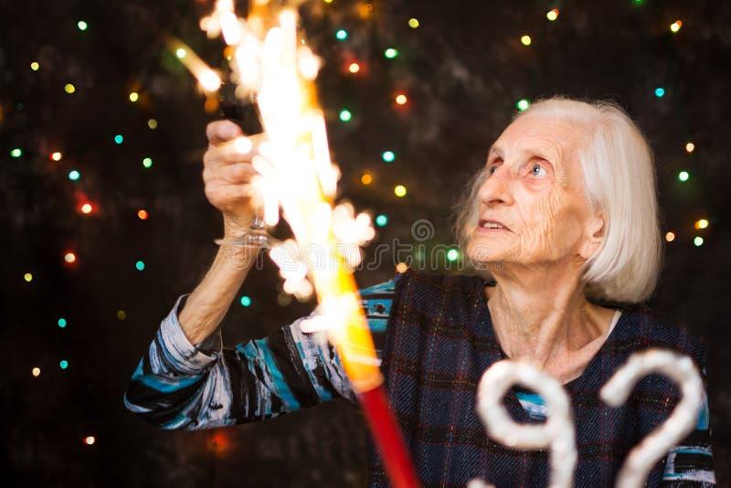 Starsza kobieta wznosi toast na jej przyjęciu urodzinowym zdjęcia royalty free