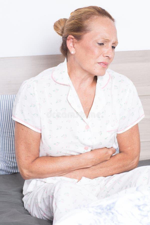 Starsza kobieta z żołądków problemami zdjęcie stock