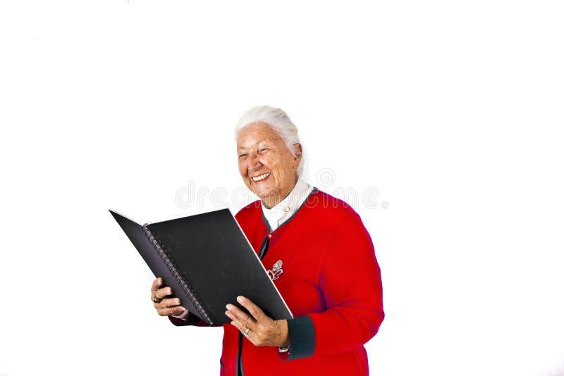 Starsza kobieta z białego włosy czytaniem w robić a i książce zdjęcie royalty free