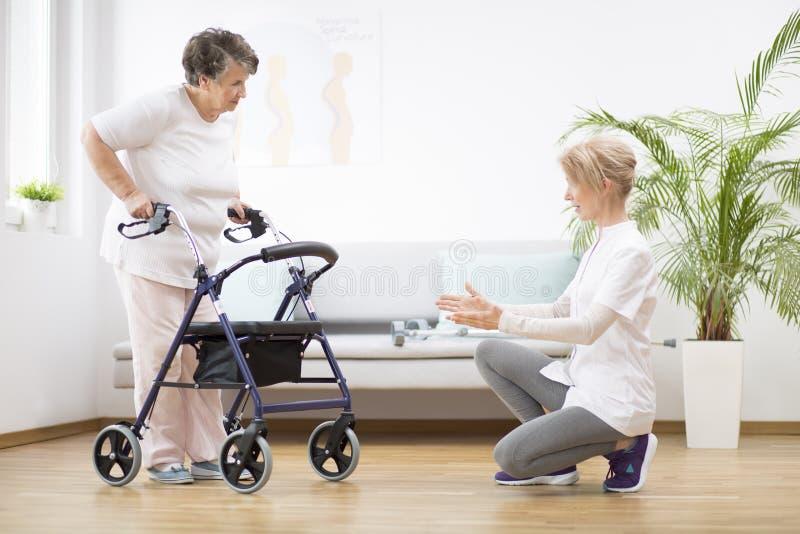 Starsza kobieta z chodzikiem, próbujÄ…ca znów chodzić i pomocna fizjoterapeutka wspierajÄ…ca jÄ… zdjęcie stock