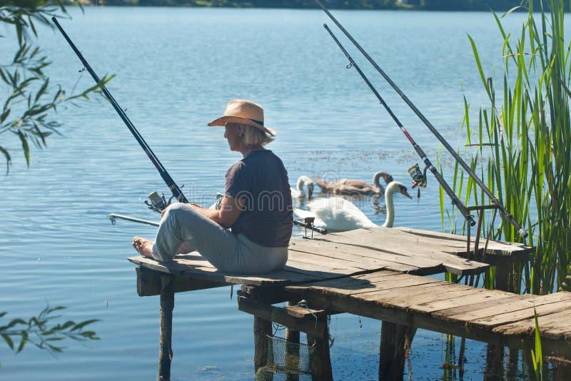 Starsza kobieta z kapeluszowym połowem na jeziorze obrazy royalty free