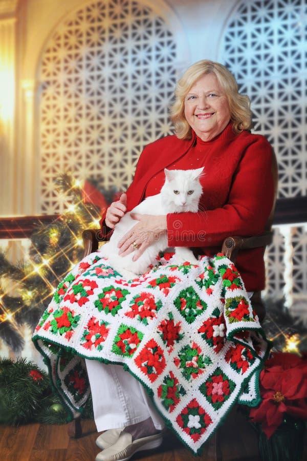 Starsza kobieta z kotem przy Christmastime obraz stock