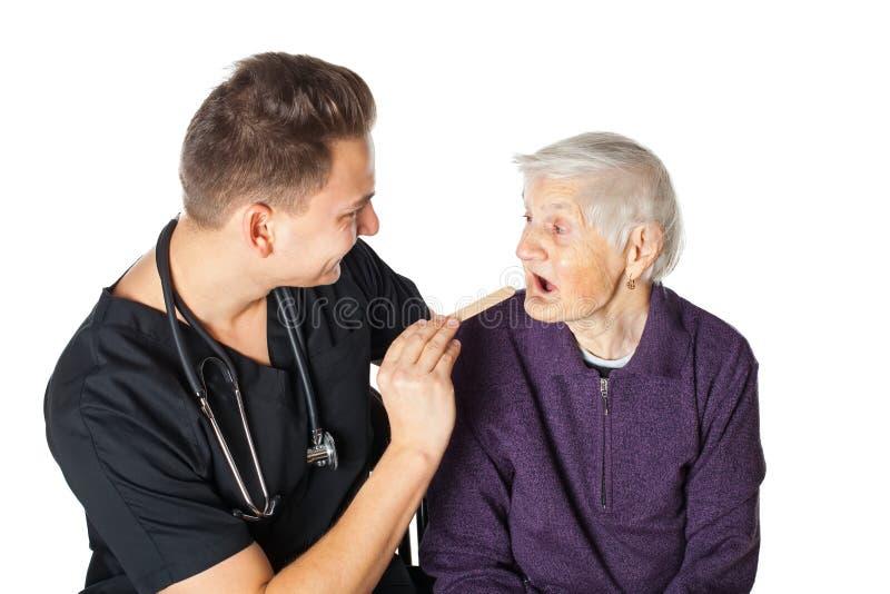 Starsza kobieta z lekarzem na odosobnionym zdjęcia stock
