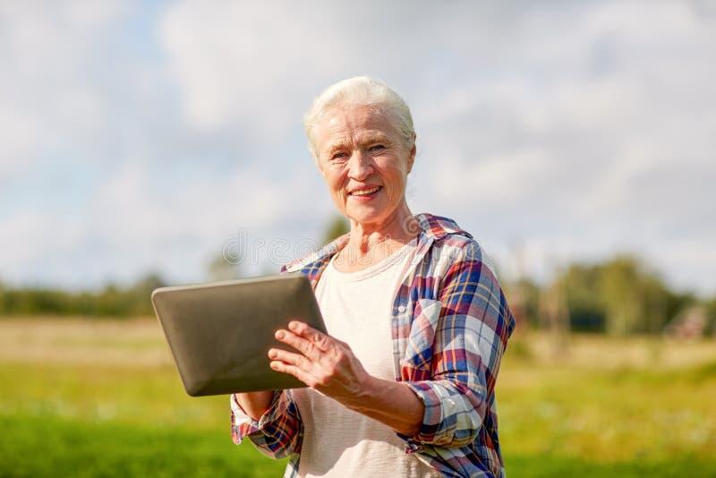 Starsza kobieta z pastylka komputeru osobistego komputerem przy okręgiem administracyjnym obraz stock