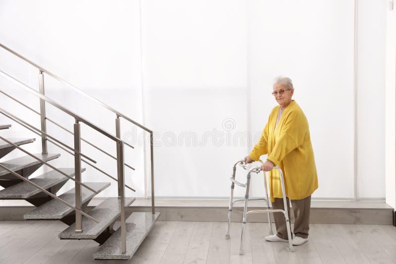 Starsza kobieta z piechurem blisko schodków fotografia royalty free