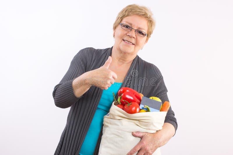 Starsza kobieta z torba na zakupy i kredytową kartą pokazuje aprobaty, płaci dla robić zakupy obraz stock