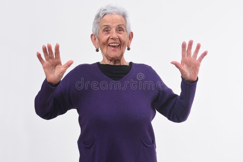 Starsza kobieta z zdziwioną twarzą podnosić rękami na białym tle i fotografia royalty free