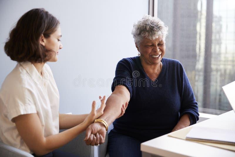 Starsza kobieta Zaszczepia Z Grypowym dźgnięciem kobiety lekarką W Szpitalnym biurze zdjęcie stock