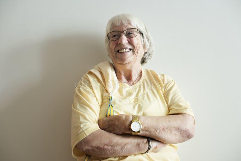 Starsza kobieta zbroi krzyżuje i ono uśmiecha się fotografia stock