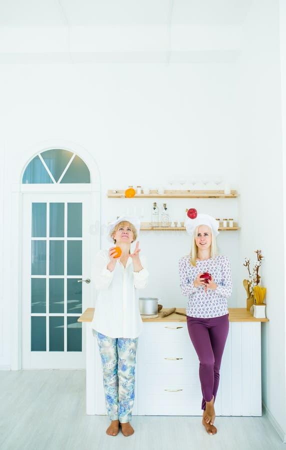 Starsza kobiety i blondynki dziewczyna w kucbarskich kostiumach w kuchennego łasowania świeżej owoc fotografia royalty free