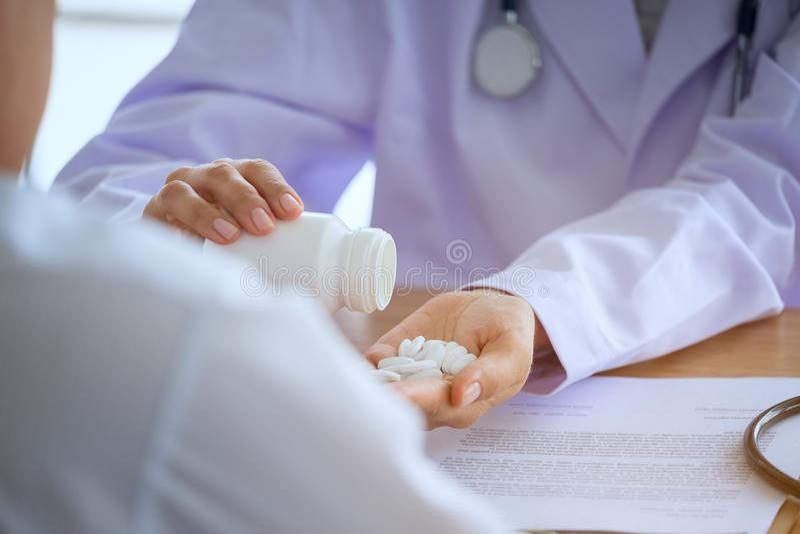 Starsza kobiety lekarka konsultuje młodego Cierpliwego obsiadanie przy lekarką obrazy royalty free